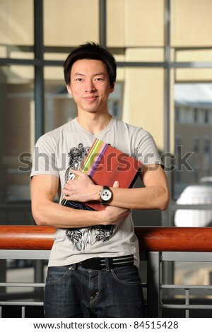 Portrait of Asian student holding book indoors