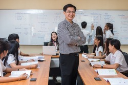 Portrait of Asian teacher standing when Giving Lesson to group of College Students in the classroom, University education concept