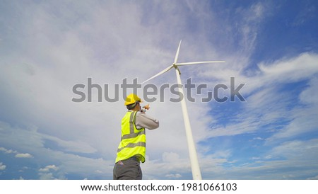 Portrait of Asian windmill engineer man, worker working on site at wind turbines field or farm, renewable clean energy source. Eco technology for electric power. industry nature environment. People Foto stock ©