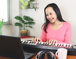 Portrait of Asian woman learning music lesson online , playing piano and looking at  computer notebook.  Teaching or learning online, social distancing and new normal.