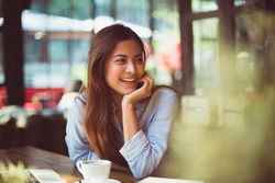 Portrait of Asian woman smiling in coffee shop cafe vintage color tone