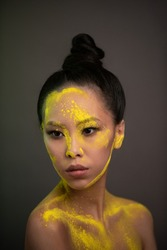 Portrait of asian woman with yellow powder paint on her face