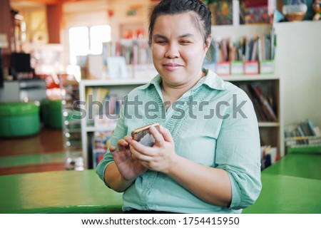 Portrait of Asian young blind person woman using smart phone with voice accessibility for persons with disabilities in creative workplace