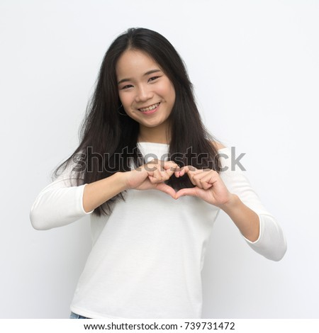 portrait of asian young girl smiling with heart shape hand sign isolated on white background #739731472