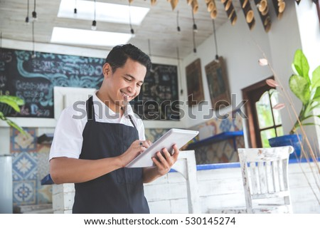 Shutterstock portrait of asian young male cafe owner with tablet