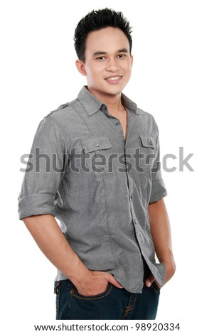 Portrait of asian young man standing with his hands in pocket against white background - stock photo