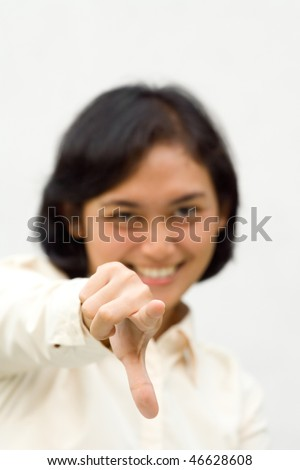 portrait of asian young woman smiling and pointing her index finger at you. choose you.