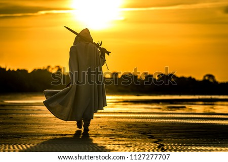 Portrait of assassin in white costume with the sword at the sea. He is posing at the sea during beautiful sunset. Yellow, soft light. #1127277707