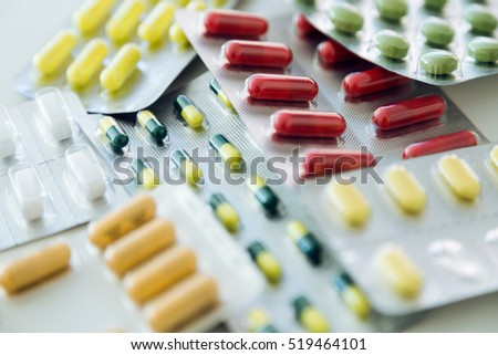 Portrait of assorted pharmaceutical medicine pills, tablets and capsules on the table.