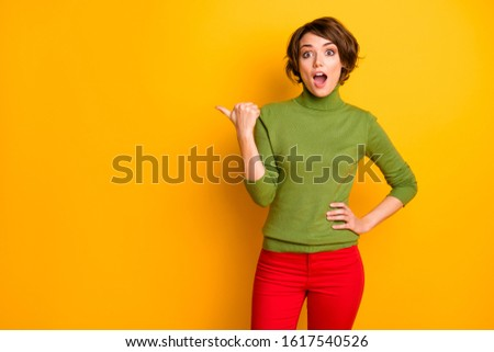 Portrait of astonished crazy girl point forefinger copyspace impressed wonderful adverts promotion scream wow omg recommend select wear red green outfit isolated bright color background