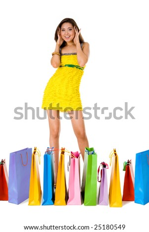 Portrait of astonished female in yellow glamorous dress with colorful paperbags in front