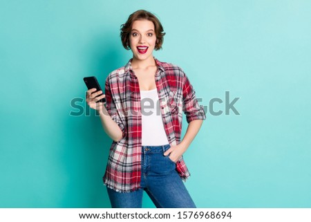 Portrait of astonished girl blogger use smart phone get social network notification impressed scream wow omg wear stylish outfit denim isolated over teal color background