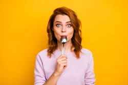 Portrait of astonished inspired girl have weekend in restaurant taste dish enjoy lick spoon impressed stare stupor wear pink jumper isolated over yellow color background