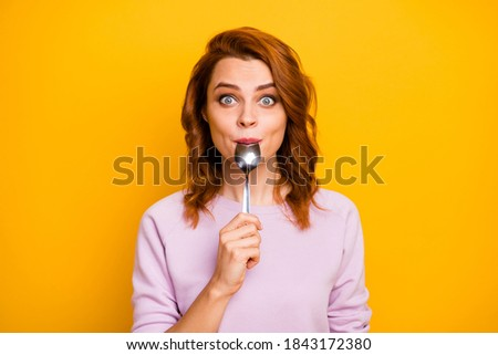 Portrait of astonished inspired girl have weekend in restaurant taste dish enjoy lick spoon impressed stare stupor wear pink jumper isolated over yellow color background Foto d'archivio ©