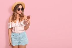 Portrait of astonished pretty woman wearing blouse with bared shoulders, short, straw hat and sunglasses, holds smart phone with surprised facial expression, checking social network, has shocking news