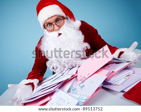 Portrait of astonished Santa Claus holding letters and looking at them in trouble