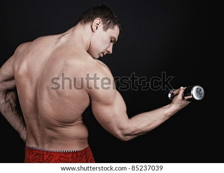 Portrait of athlete male with dumbbell isolated on black background