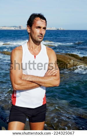 Portrait of athlete standing on sea rocks at sunny summer day while resting after intensive training outdoors, exhausted fit runner after workout resting on seaside, healthy lifestyle concept