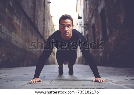 Portrait of athletic handsome caucasian man making push ups in urban setting. Young male runner warm up before start his morning workout training