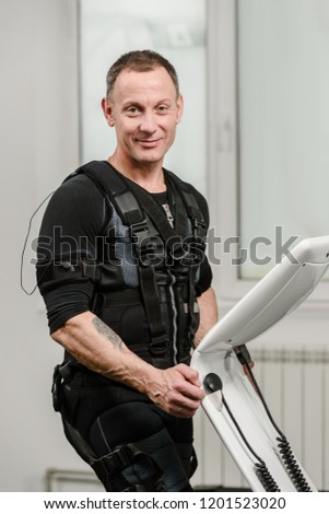 Portrait of athletic man in EMS suit near electro muscle stimulation machine #1201523020