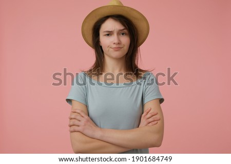 Portrait of attractive, adult girl with long brunette hair. Wearing blueish t-shirt and hat. Folds her hands on a chest. Incredulously watching at the camera isolated over pastel pink background Сток-фото ©