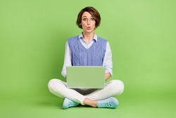 Portrait of attractive amazed girl sitting lotus position using laptop pout lips e-commerce news isolated over green color background