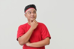Portrait of attractive Asian man in t-shirt with red and white ribbon on head, standing against gray background, thinking about question with hand on chin