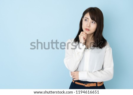 portrait of attractive asian woman on blue background