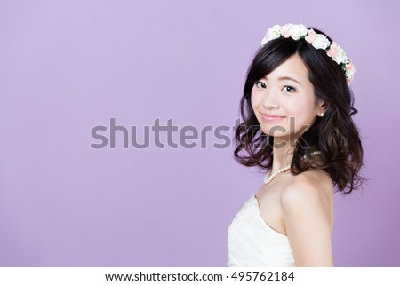 portrait of attractive asian woman wearing wedding dress isolated on purple background #495762184
