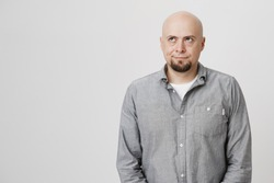 Portrait of attractive bald man looking up being distracted and pensive over white background. Handsome guy works as vloger was in the middle of speech when loud noise appeared. Person is annoyed.
