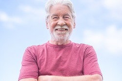 Portrait of attractive bearded senior man with crossed arms, looking at camera. Bright sky in background