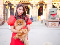 Portrait of attractive beautiful  asian young woman wear traditional Chinese cheongsam decoration and holding dog in  the shrine.For human and a dog, Girl and her friend dog concept.