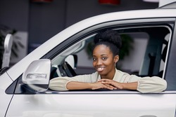 portrait of attractive black lady in car, africanamerican woman looks at camera and smile, she likes design inside of car and want to get it in dealershp