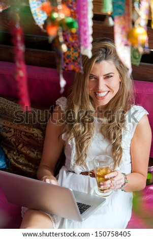 Portrait of attractive blond relaxing with cup of tea and laptop. - stock photo
