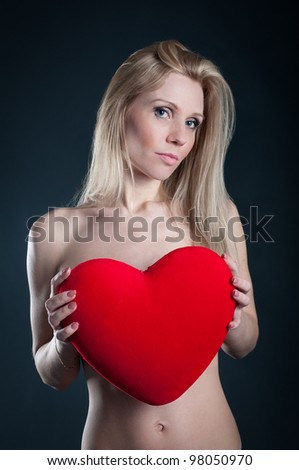 Portrait of attractive blond woman with heart against black background.