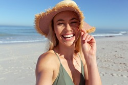 Portrait of attractive blonde Caucasian woman enjoying time at the beach on a sunny day, wearing a sun hat, looking at camera, with blue sky and sea in the background. Summer tropical beach vacation.