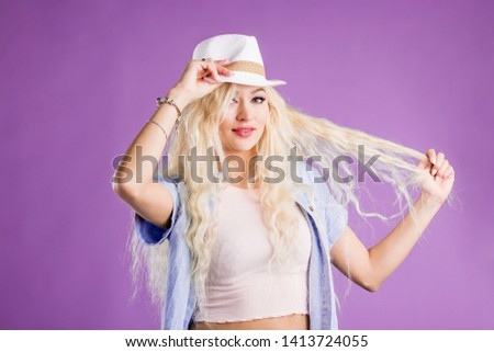 Portrait of attractive blonde girl touching her straw hat and long blonde hair posing in studio on lilac background. She wears denim shirt, tee shirt, white hat, jewelry, smiling to camera.