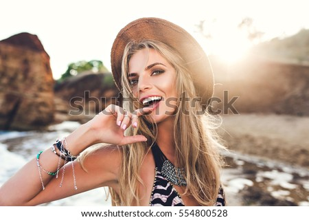 Stock Photo Portrait of attractive blonde girl with long hair posing on rocky beach on sunset background. She wears bikini, hat. She holds finger on lips and looks to the camera.