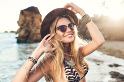 Portrait of attractive blonde girl with long hair posing on rocky beach. She wears bikini, hat, sunglasses. She is smiling.