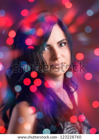 Portrait of attractive brunette girl with bokeh lights on background