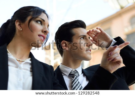 Portrait of attractive businessman and businesswoman looking at something interesting. Couple working.