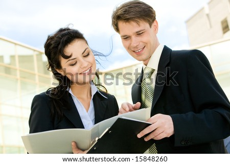 Portrait of attractive businesspeople discussing a plan at meeting on the street