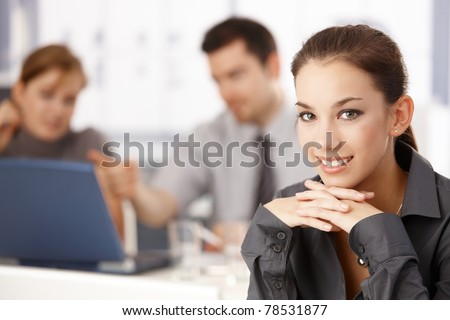 Portrait of attractive businesswoman sitting at meeting table, colleagues working in the background.?