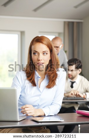 Portrait of attractive businesswoman sitting at office in front of laptop and working online. Mature woman looking away and smiling.