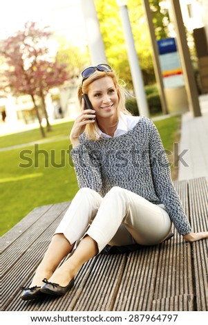 Portrait of attractive businesswoman sitting at office park and making call.