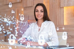 Portrait of attractive businesswoman working with documents and thinking how to protect clients confidential information and cyber security. IT hologram padlock icons over office background.