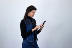 Portrait of attractive caucasian middle age woman holding phone, reads whatsapp, isolated on gray background studio shot, black sweater, denim jacket, jeans, dark air. Place for your text in copy spac