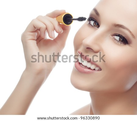 portrait of attractive  caucasian smiling woman isolated on white studio shot applying mascara looking at camera