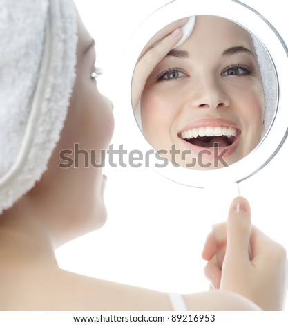 portrait of attractive  caucasian smiling woman isolated on white studio shot cleaning her face looking at the mirror