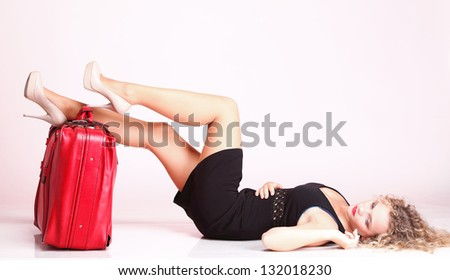 portrait of attractive caucasian woman blond wait red suitcase and rose